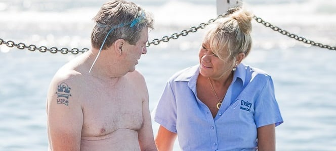 Living with Dementia, Care worker and client beside ocean pool