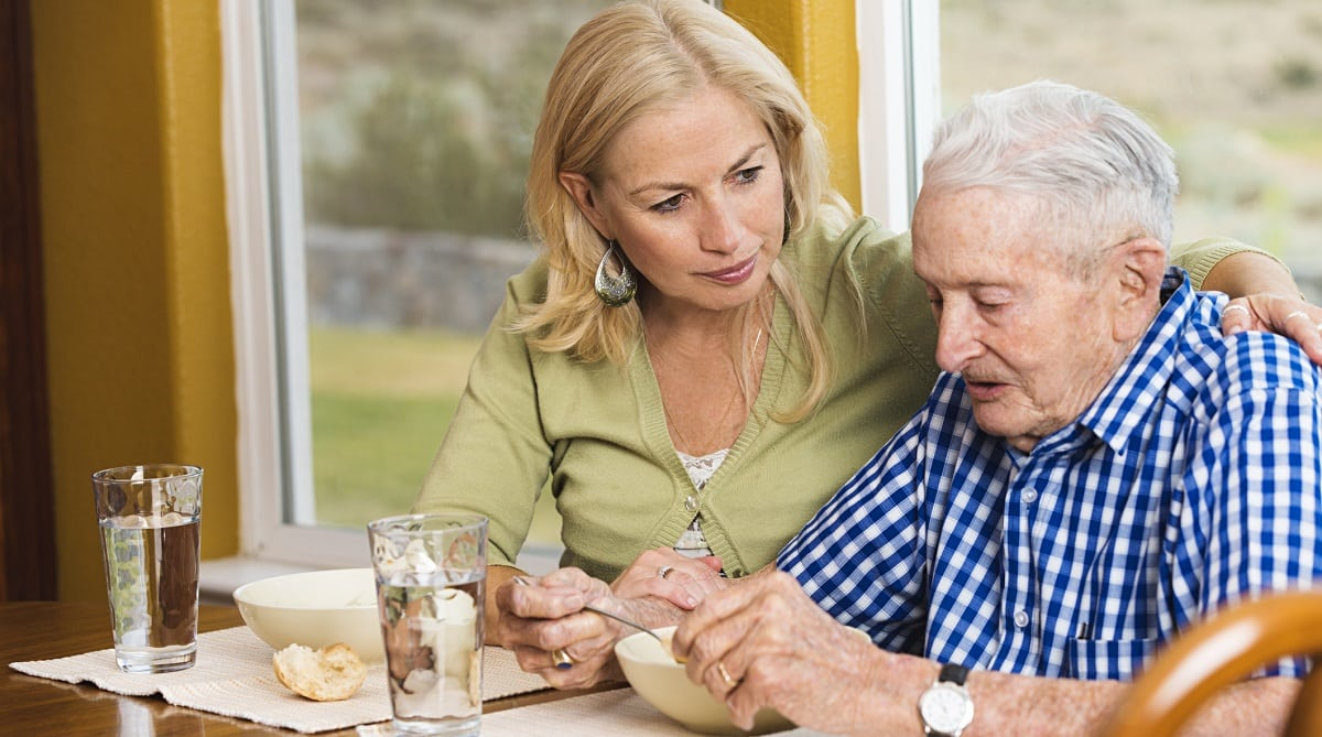 A caring daughter watching her father eat soup, home care, Oxley Home Care